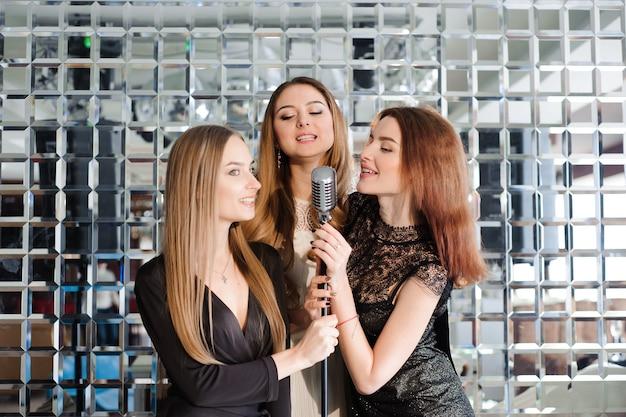 Happy girls having fun singing at a party.