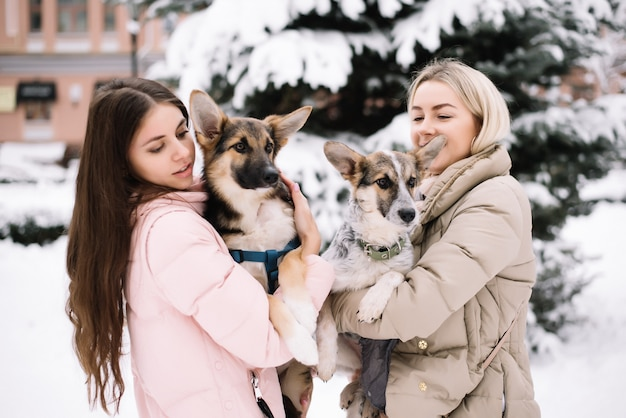 Happy girls holding lovely dogs in hands