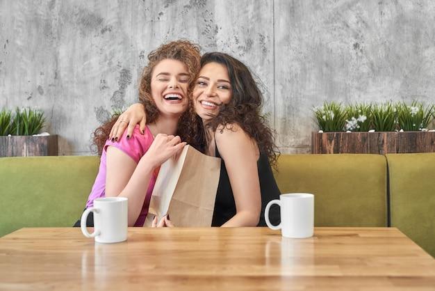 幸せな女の子を抱いて、カフェに存在する紙袋を保持しています。