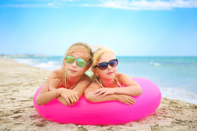 Happy girls lying on pink inflatable circle at the beach