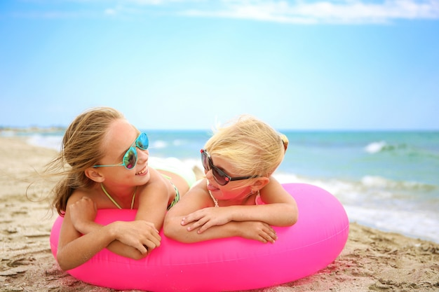Happy girls lying on pink inflatable circle.