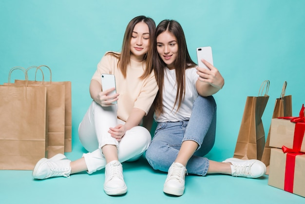ショッピングバッグで自分撮りを作る幸せな女の子。写真を撮るカラフルなカジュアルな服を着て2人の女の子の笑顔