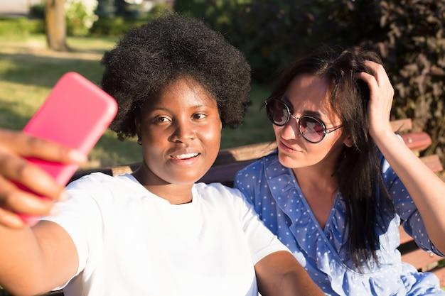 다양한 국적의 행복한 소녀들이 여름에 셀카를 찍습니다.