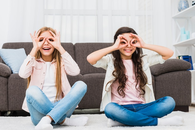 Happy girls sitting on carpet doing ok gesture like binoculars