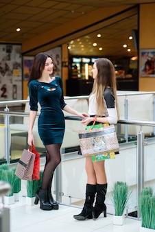 Счастливые девушки улыбаются и делают покупки в торговом центре