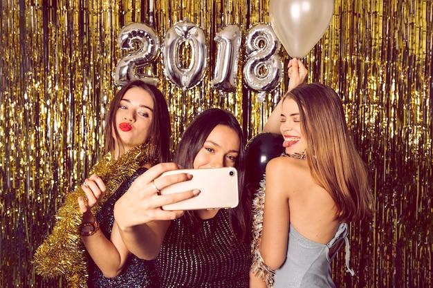 Ragazze felici che prendono selfie sulla celebrazione del nuovo anno