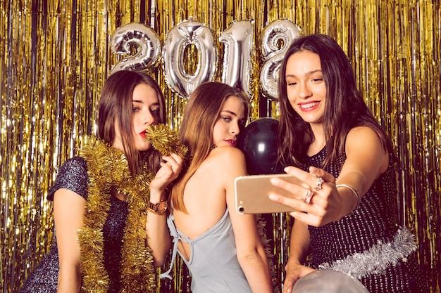 Ragazze felici che prendono selfie sul partito di nuovo anno