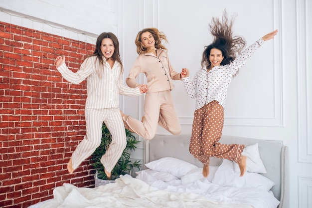 Happy girls. three young girls jumping on bed and feeling happy