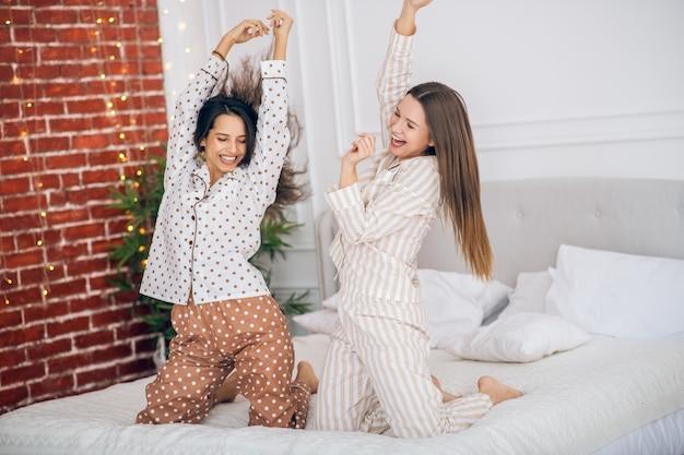 행복한 소녀들. 침실에서 재미 잠 옷에 두 어린 소녀