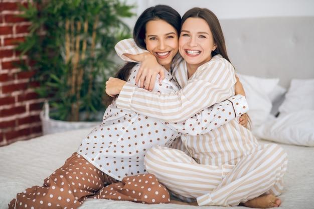 Счастливые девушки. две молодые девушки в пижамах обнимают друг друга и выглядят счастливыми