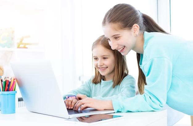 明るい部屋でコンピューターに取り組んでいる幸せな女の子