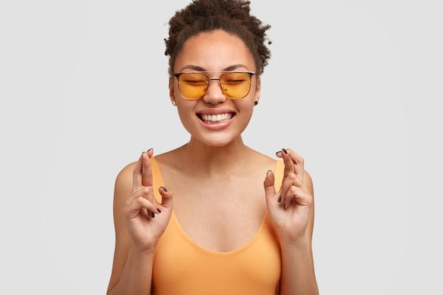 ポジティブな笑顔で幸せな嬉しい暗い肌の女性、幸運のために指を交差させ、流行の色合いを身に着け、目を閉じたままにし、白い壁に向かってポーズをとります。美しい陽気なアフリカ系アメリカ人の女性