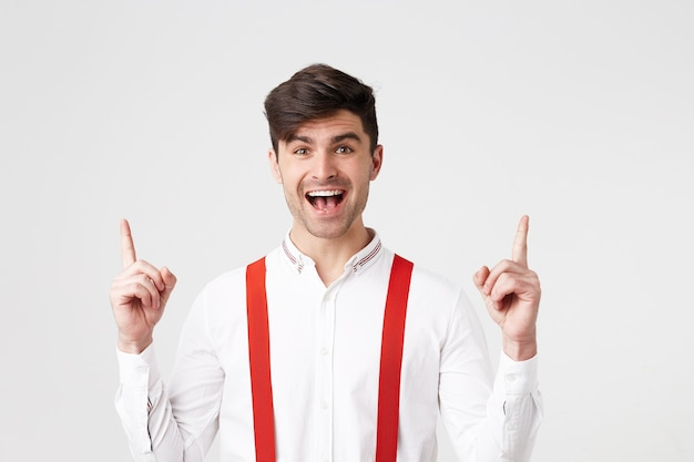 Happy glad handsome guy,looks amazed excited,dressed in white shirt and red suspenders, points with index fingers upwards