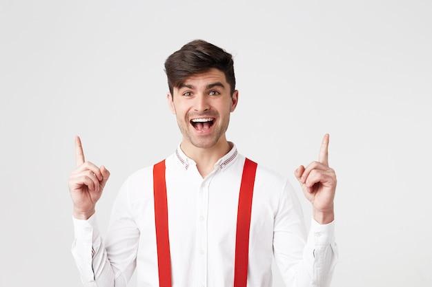 Felice bel ragazzo felice, sembra stupito eccitato, vestito con camicia bianca e bretelle rosse, punta con l'indice verso l'alto