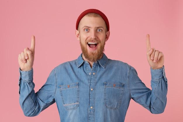 Felice felice contento giovane ragazzo barbuto guarda con eccitazione e ha aperto la bocca, tiene le mani in alto e punta con le dita anteriori verso l'alto sullo spazio della copia, vestito con una camicia di jeans, isolato