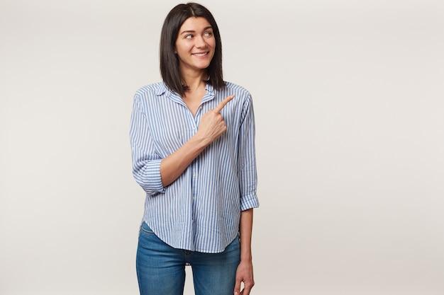Felice felice felice giovane bruna guarda con eccitazione nell'angolo in alto a destra e sorride e punta il dito indice lì sullo spazio della copia, vestito con una camicia, isolato