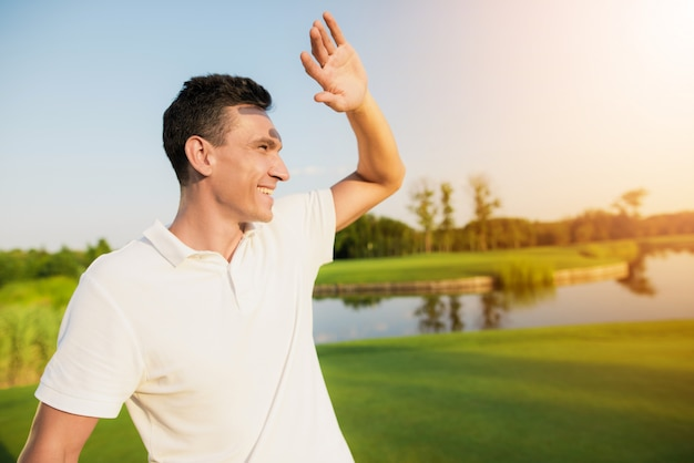 Happy golf player in white clothing in the sun.