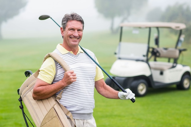 Happy golfer with golf buggy behind