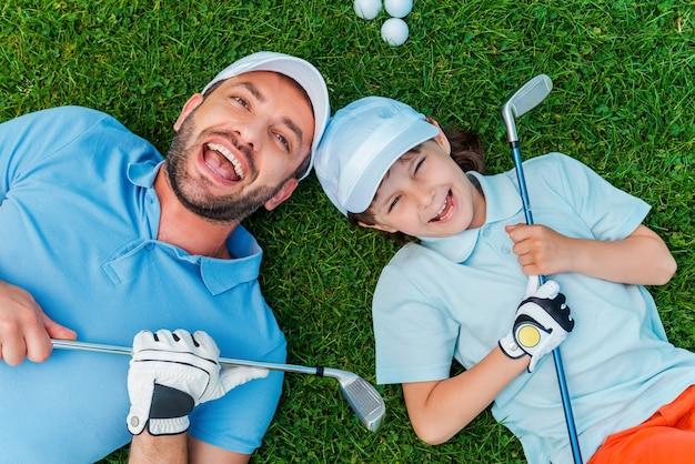 幸せなゴルファー。ゴルフクラブを保持し、緑の芝生の上に横たわっている間笑顔で陽気な小さな男の子と彼の父の上面図