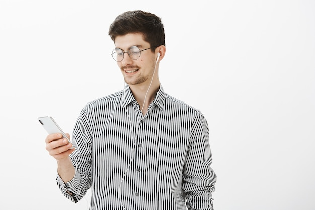 Happy good-looking caucasian bearded guy in round glasses, holding smartphone and listening music in earphones, using gadget to find cafe on map, standing carefree and relaxed