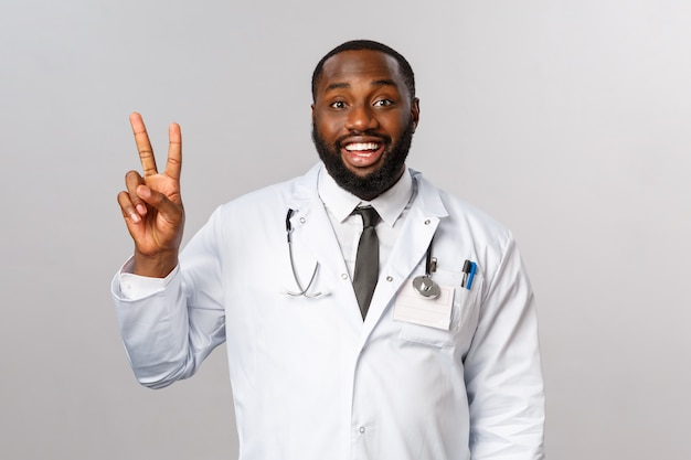幸せそうに見える、熱狂的なアフリカ系アメリカ人の男性医師は患者の病気を治療する方法を説明します
