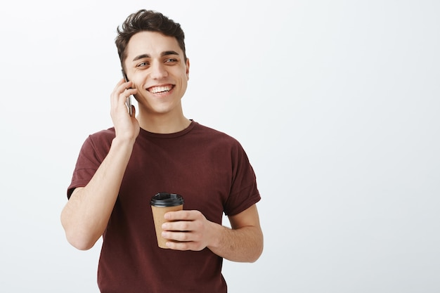 電話で話している赤いtシャツの幸せな見栄えの良い男性
