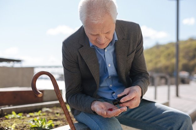 Счастливый красивый пожилой джентльмен, опуская палку и опорожняя бутылку с лекарствами, сидя на клумбе.