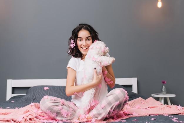 幸せな朝、ベッドの上のピンクのティンセルの小さな犬を楽しんでブルネットの巻き毛のパジャマで若いうれしそうな女性の真の肯定的な感情