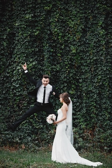 Happy gorgeous bride and stylish groom jumping and having fun fun and crazy brides