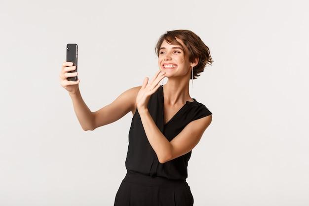 Счастливая великолепная женщина, имеющая видеозвонок, махнув рукой на камеру смартфона и улыбаясь, стоя на белом.