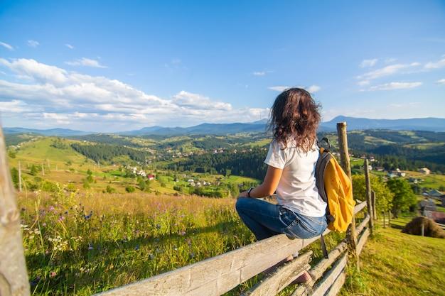 Счастливая великолепная девушка наслаждается видом на холмы, сидя в цветочном поле на холме с захватывающим дух пейзажем.