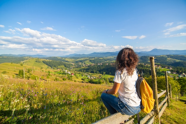 幸せなゴージャスな女の子は、息をのむような自然の風景と丘の上の花畑に座って丘の景色をお楽しみください。