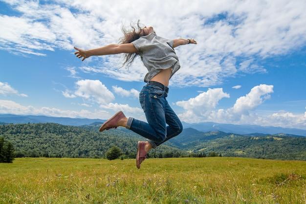 幸せなゴージャスな女の子は息をのむような山の風景と丘の上にジャンプする山の景色をお楽しみください