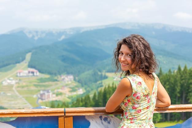 幸せなゴージャスな女の子は、息をのむような山の風景と丘の上の夏のドレスで山の景色の滞在をお楽しみください。