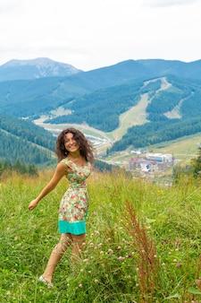 幸せなゴージャスな女の子は息を呑むような山の風景と丘の上の夏のドレスで山の景色の滞在をお楽しみください