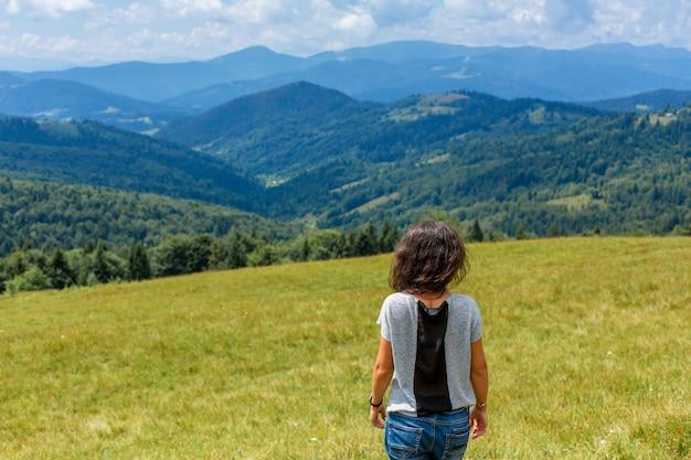 幸せなゴージャスな女の子は息を呑むような山の風景と丘の上に山の景色の滞在をお楽しみください