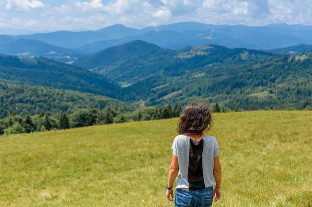 행복 한 화려한 소녀는 숨막히는 산 풍경과 함께 언덕에 산보기 숙박을 즐길 수