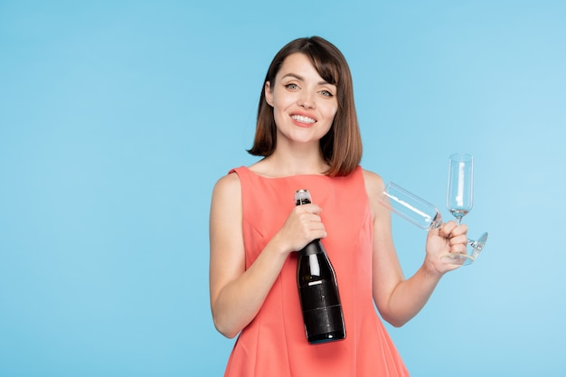Happy gorgeous girl with toothy smile holding bottle of champagne and two flutes and looking at you