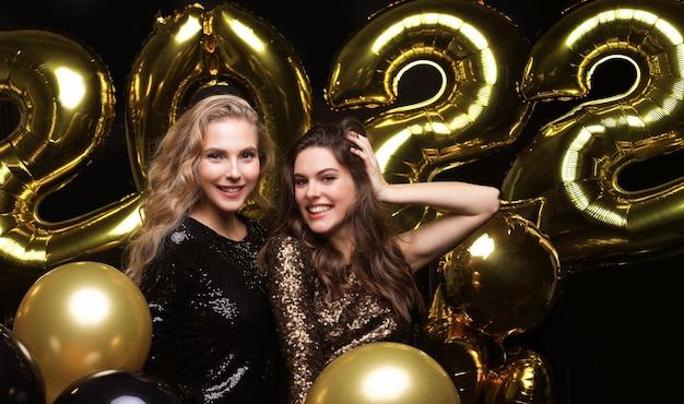 세련된 섹시한 파티 드레스를 입은 행복한 화려한 소녀들은 2022년 금색 풍선을 들고 크리스마스나 새해 전야 파티에서 즐거운 시간을 보냅니다.