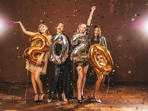 Счастливые великолепные девушки в стильных сексуальных платьях для вечеринок с золотыми и серебряными воздушными шарами 2020 года