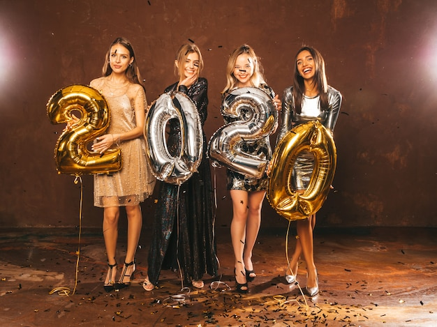Happy gorgeous girls in stylish sexy party dresses holding gold and silver 2020 balloons