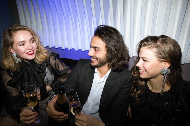 Happy gorgeous girls and young elegant man toasting with champagne in night club while enjoying party