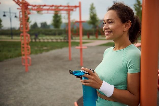 幸せなゴージャスな幸福混血アフリカ系アメリカ人の中年女性が屋外トレーニングセッションの後に水を飲み、クロスバーに寄りかかって休んでいる間歯を見せる笑顔で笑う