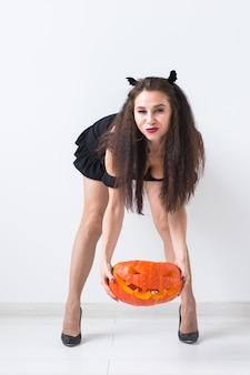 白い部屋の背景に笑みを浮かべて魔女のハロウィーンの衣装で幸せなゴシック若い女性。
