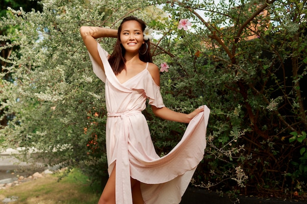 夏の晴れた日に公園を歩いて幸せな優雅なアジアの女性。
