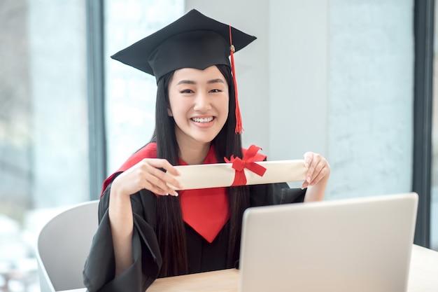 幸せな卒業生。彼女の卒業証書を保持し、幸せそうに見えるかわいいアジアの笑顔の卒業生
