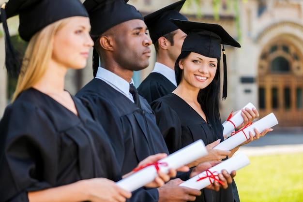 幸せな卒業生。 4人の大学卒業生が並んで立って卒業証書を持っており、1人の女性がカメラを見て笑っている