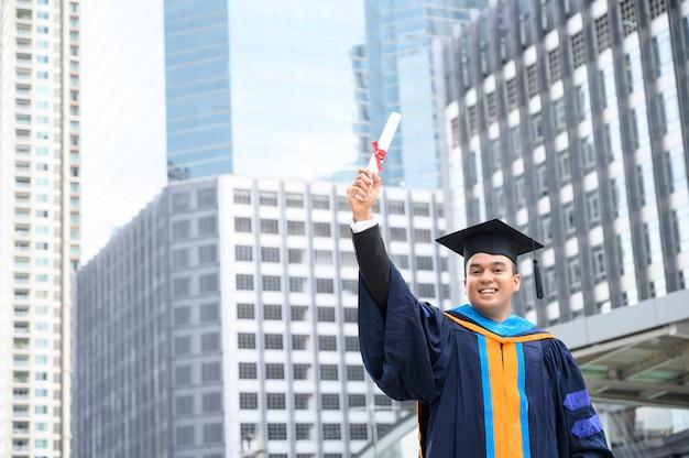 Счастливый выпускник. счастливый азиатский человек в мантиях градации держа диплом в руке на городском городе.