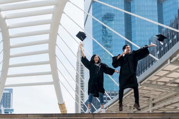 Счастливый выпускник подростков, прыгая с выпускными платьями
