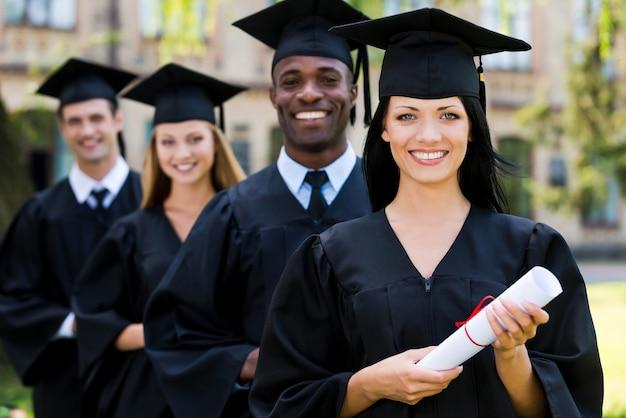 幸せな卒業生。 4人の大学卒業生が一列に並んで笑っている